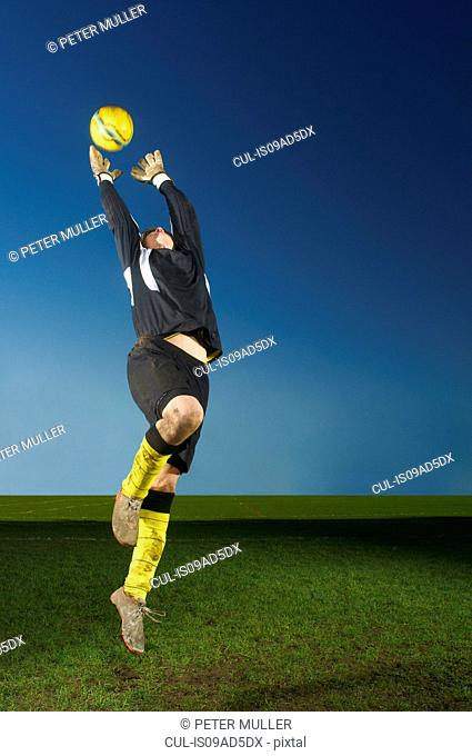 Goalkeeper jumping to catch football