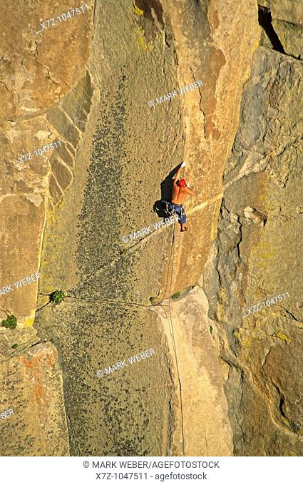 Man rock climbing a route called Strategic Defense which is rated 5,11 and located on Morning Glory Spire at The City Of Rocks National Reserve in southern...