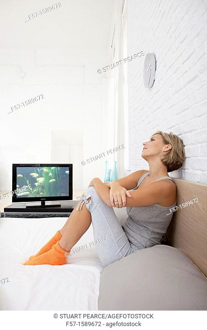 Young woman chilling out on her bed watching TV