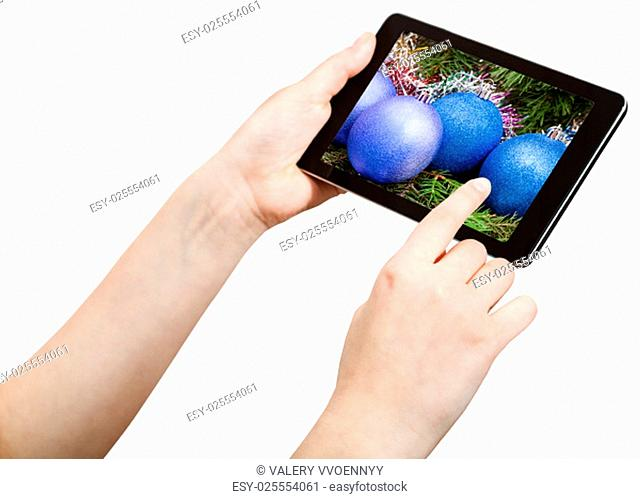 hand touches tablet pc with Christmas decorations on screen isolated on white background