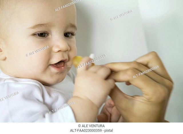 Baby taking pacifier from mother's hand, close-up