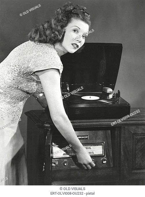 Woman playing record album on phonograph (OLVI008-OU232-F)