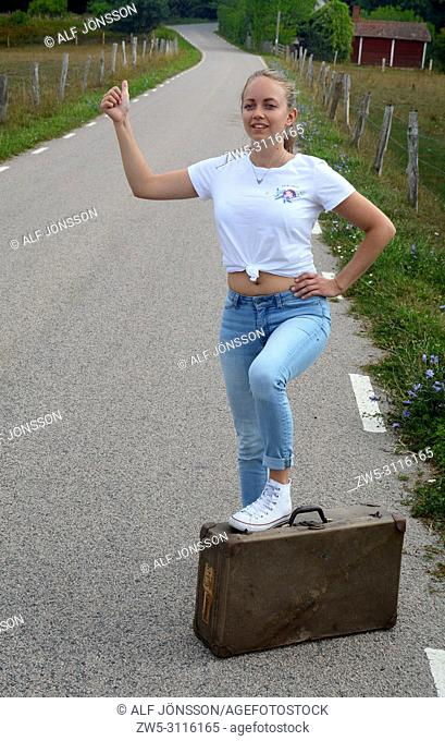 Hitch-hiking young woman, 25 years old, on a countryroad in Scania, Sweden; Europe, standing with one foot on an old suitcase