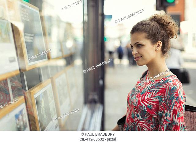 Young woman browsing real estate listings at urban storefront