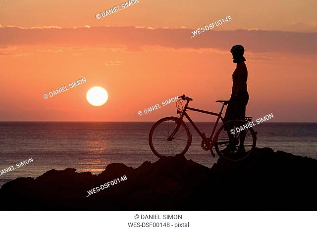 Italy, Tuscany, Albegna, Female mountainbiker taking a break at sunset