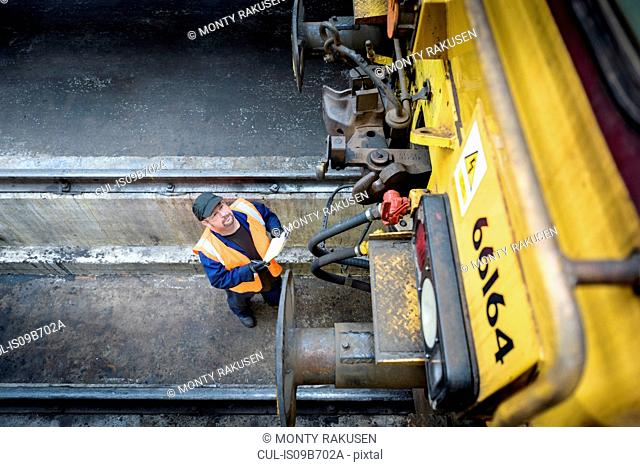 Engineer inspecting locomotive in train works, high angle view