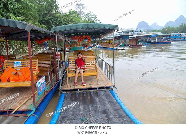 Boy waiting for a ride in a bamboo raft on the Li River, Yangshuo, China