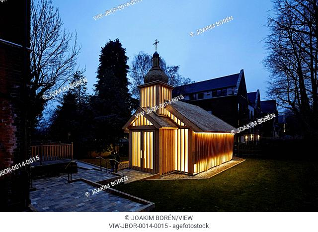 Dusk view of timber church in garden. Belorussian Memorial Chapel, London, United Kingdom. Architect: Spheron Architects, 2016