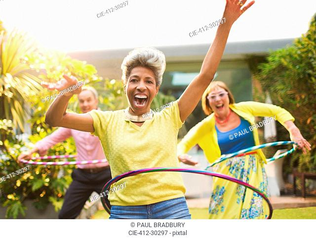 Portrait playful mature adults spinning with plastic hoops in garden