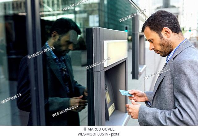 Businessman taking money at an ATM in the city