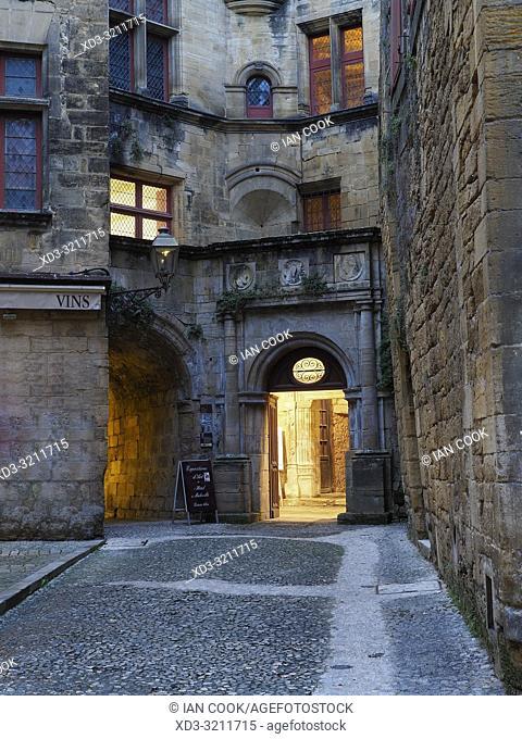 empty street with lighted doorway, Sarlat-la-Caneda, Dordogne Department, Nouvelle-Aquitaine, France