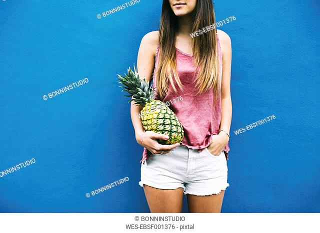 Young woman standing with pineapple at blue wall