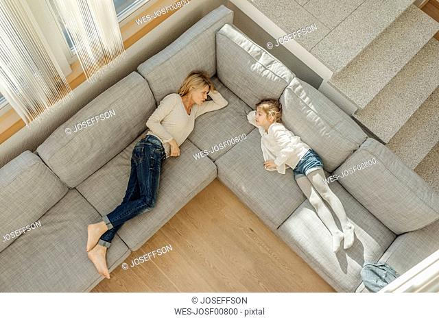 Mature woman and girl at home lying on couch