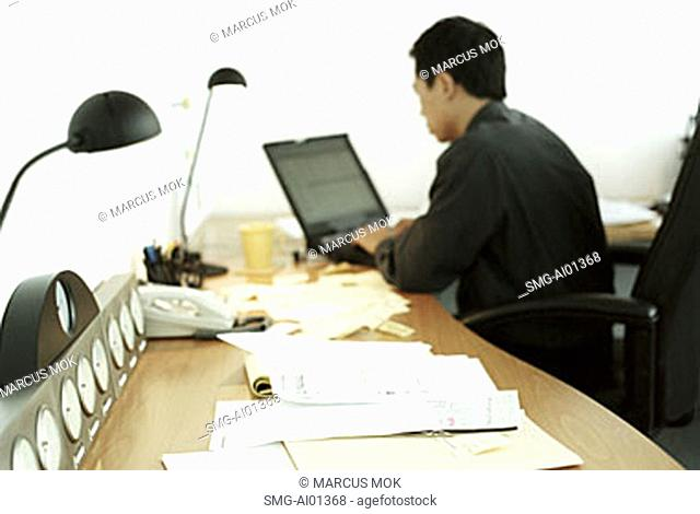 Male executive working on laptop, rearview