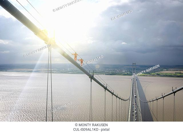 Bridge workers walking on cable of suspension bridge under bright sunlight. The Humber Bridge, UK was built in 1981 and at the time was the world's largest...