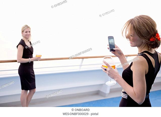 Laughing woman taking a picture of her friend on deck of a cruise liner