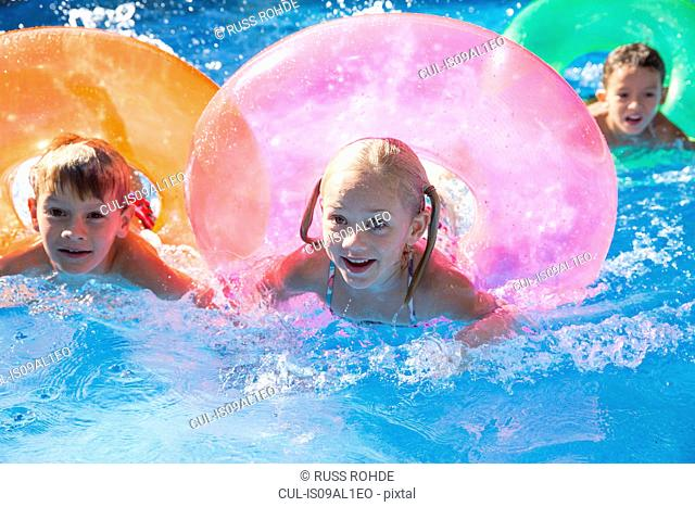 Three children swimming with inflatable rings in garden swimming pool