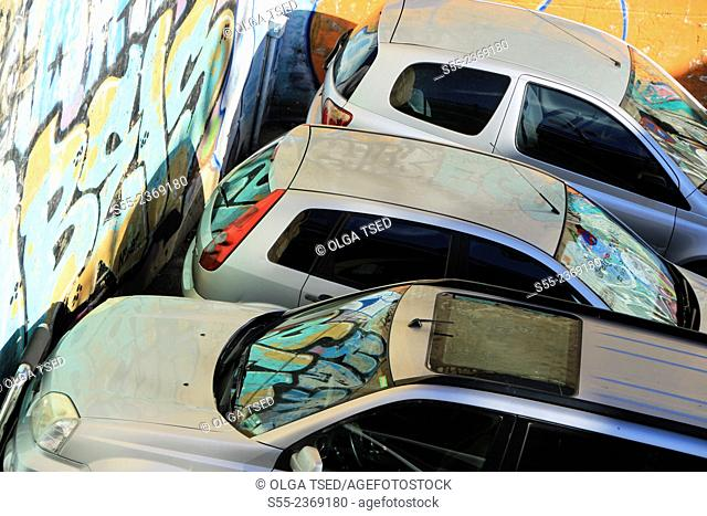 Cars parked in the street next to graffiti wall. Barcelona, Catalonia, Spain