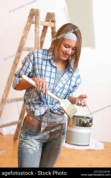 Home improvement: Smiling woman with paint and brush painting wa