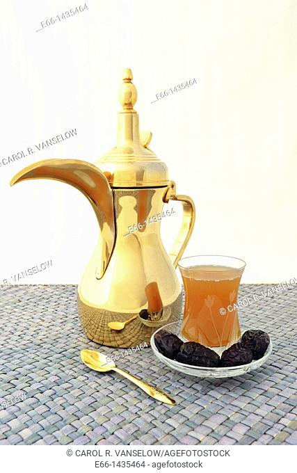 dallah Arabic coffee pot with cup of Arabic coffee and dates