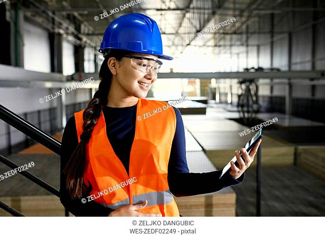 Smiling female worker using tablet in factory warehouse