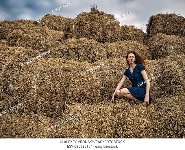 Red-haired girl in a light summer dress of blue color sits on a stack of straw. The girl's hair develops in the wind. The girl is dressed summer dress above the...