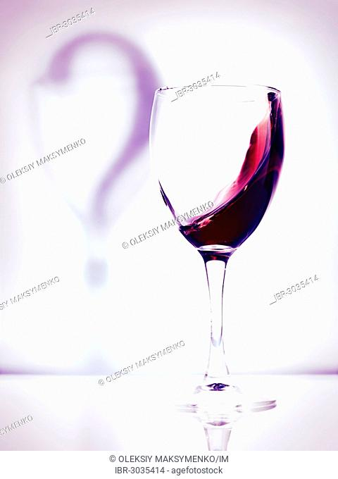 Red wine in a glass and a question mark shadow