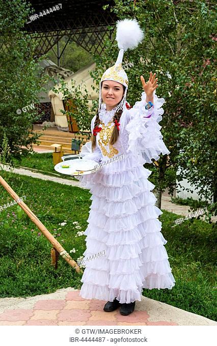 Kazakh woman meeting guests with candies, Kazakh ethnographic village aul Gunny, Talgar, Almaty, Kazakhstan