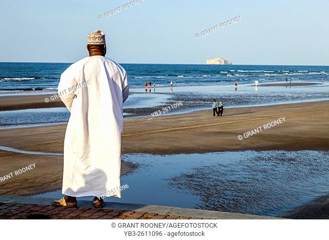 An Omani Man In Traditional Dress Looks Out Over The Beach At Muscat, Sultanate Of Oman