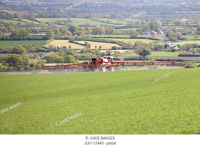 Tractor spraying pesticides on rural green crop field