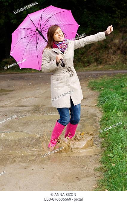 Young woman with rubber boots have fun, rainy day, Debica, Poland