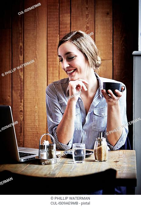 Young woman sitting in cafe holding hot drink, using laptop computer