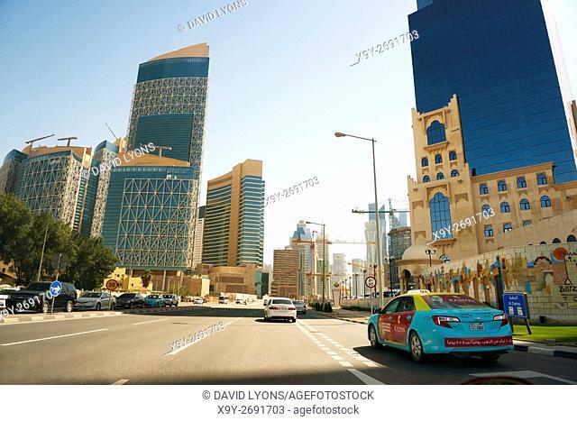 Driving into central Doha, Qatar, on Majlis Al Taawon Street. Barzan Tower on right Qatar Petroleum District complex on left