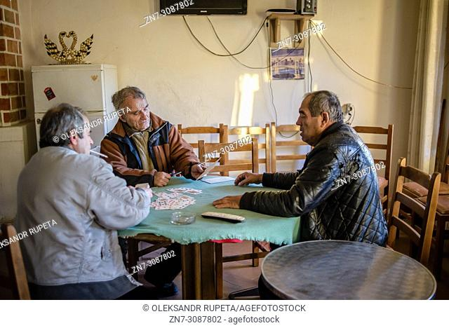 Locals play cards. Settlements by the road along the sea from Saranda to Vlora, Albania