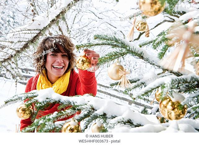 Austria, Salzburg Country, Flachau, Young woman decorating christmas tree in winter