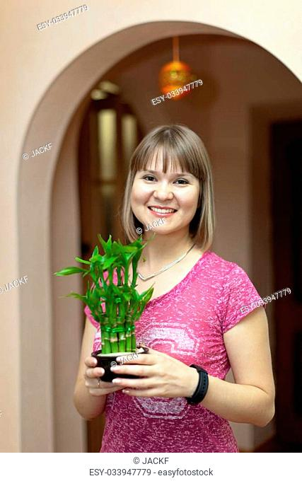 Girl with dracaena in the pot at her home