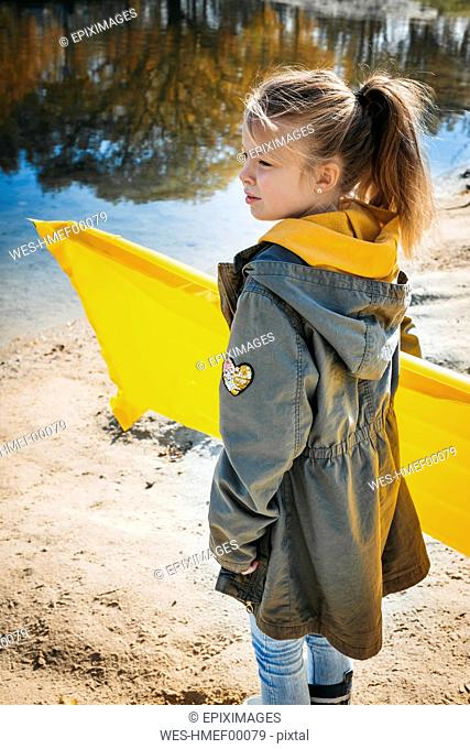 Girl with yellow airbed on the beach in autumn
