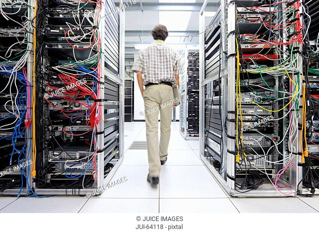 Technician walking through server room of data center