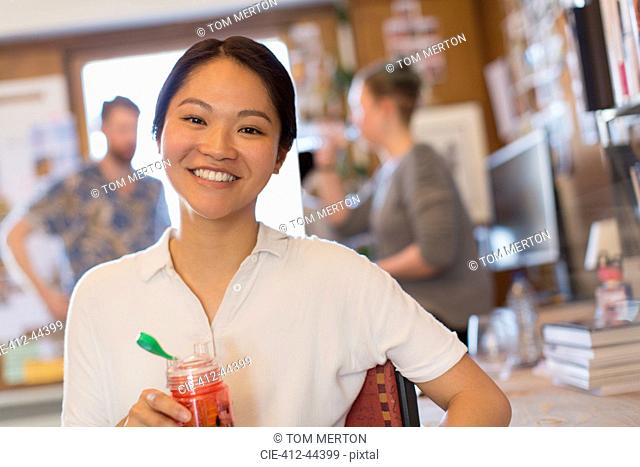 Portrait smiling creative businesswoman drinking juice in office