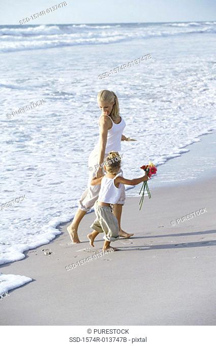 Side profile of a mother and daughter walking on the beach