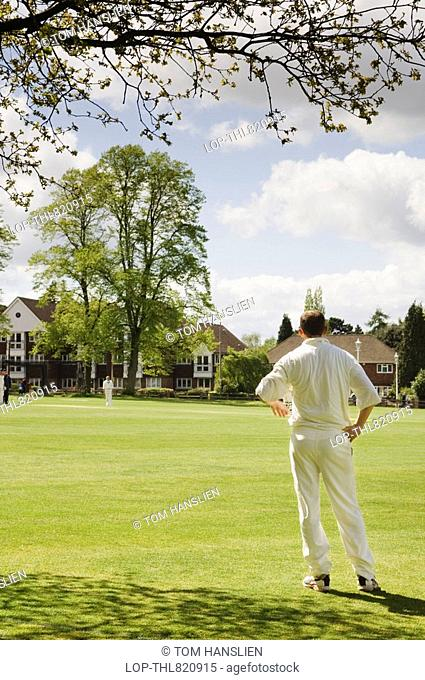 England, Kent, Sevenoaks, A cricketer fielding by the boundary on the Vine Cricket Ground in Sevenoaks