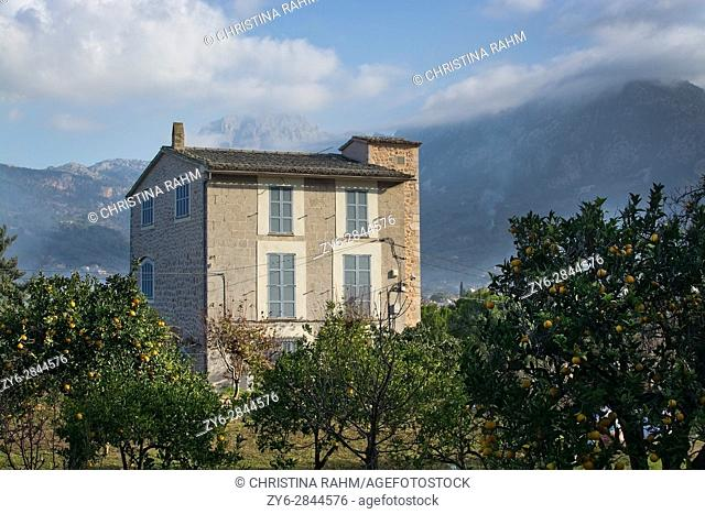 SOLLER, MALLORCA, SPAIN - JANUARY 3, 2017: Building in landscape view with cloud topped mountain, orange garden and chimney smoke on a sunny winter morning on...