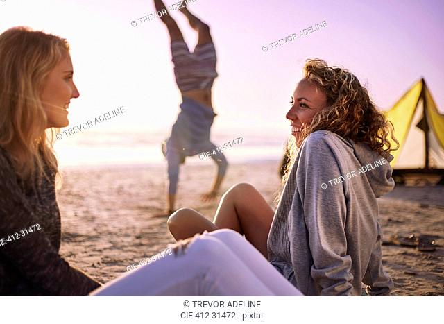 Smiling women talking on beach with man doing handstand in background