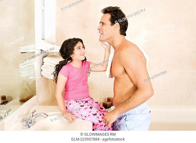 Girl applying shaving foam on her father's face