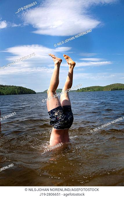 Man doing a handstand in the water, countryside of northern Sweden
