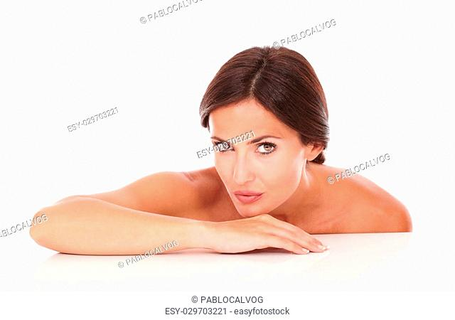 Horizontal portrait of charming young woman for skincare product looking at camera with nude shoulders on isolated white background
