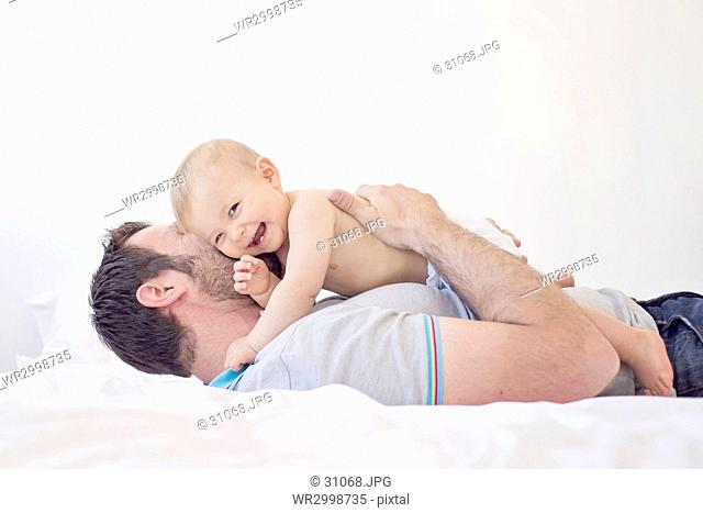 Man lying on his back on a bed, hugging smiling baby girl