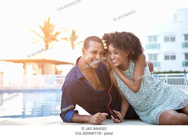 Stylish couple sharing earphones at poolside, Rio De Janeiro, Brazil