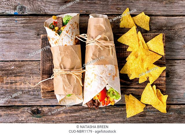 Mexican style dinner. Two papered tortillas burrito with beef and vegetables served with nachos chips over old wooden background. Flat lay