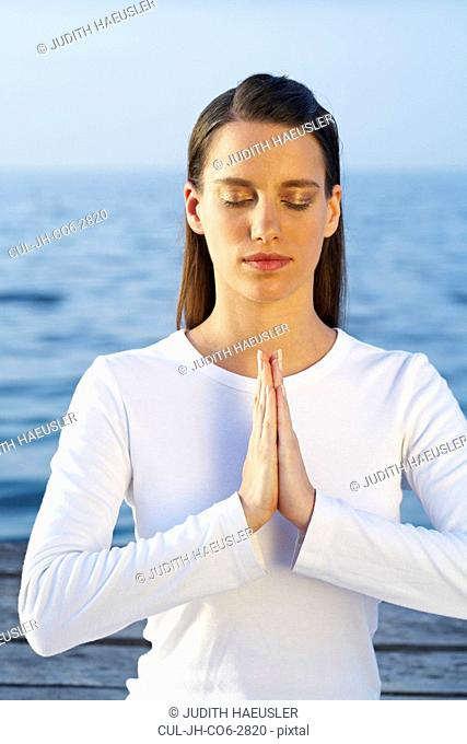 Young woman doing yoga with eyes closed by the sea